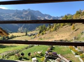 Panorama della val d'Otro (VC) con a sinistra le frazioni Follu e Dorf attraverso il graticcio della casa di Maurizio Solaro, seduto sulla sedia a sdraio a sinistra